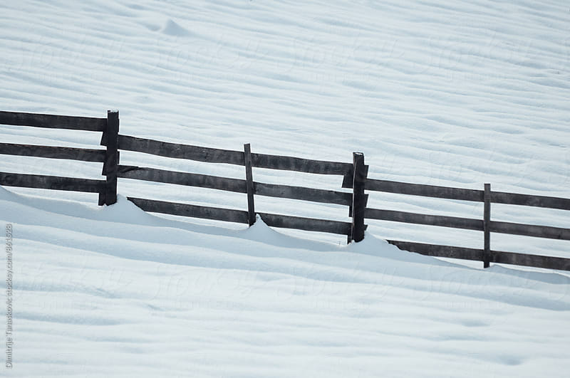 Wooden fence in the snow by Dimitrije Tanaskovic for Stocksy United