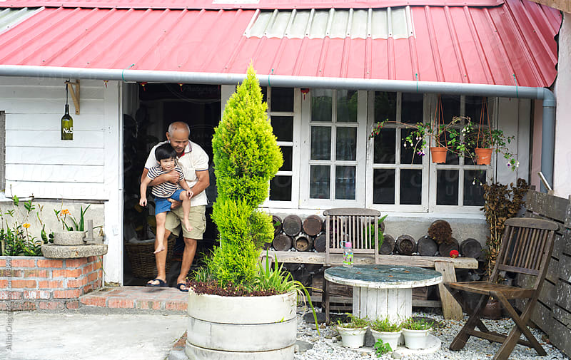 Grandfather holding grandson at rustic rural home by Alita Ong for Stocksy United