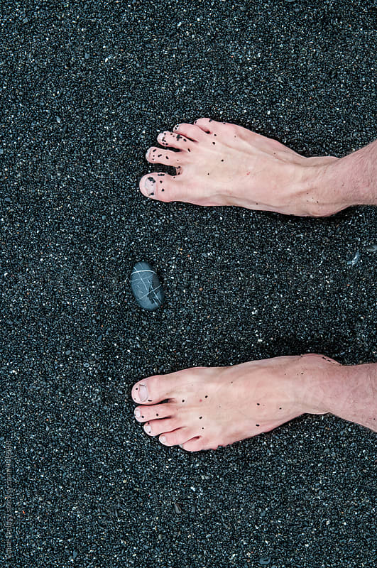 Feet in black sand by Caine Delacy for Stocksy United