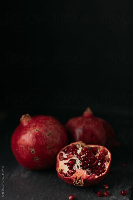 Fresh Pomegranate on slate in a dark moody kitchen by Levi Tijerina for Stocksy United