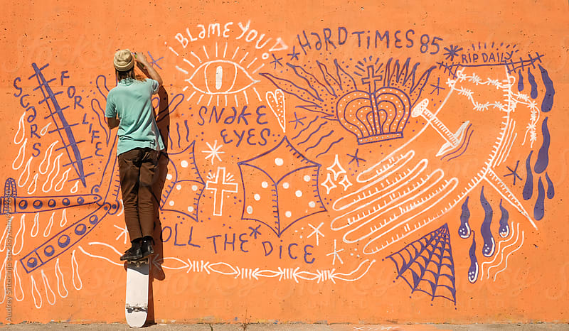 Young hip man in cool outfit  writting graffiti on orange .wall  on street. by Audrey Shtecinjo for Stocksy United
