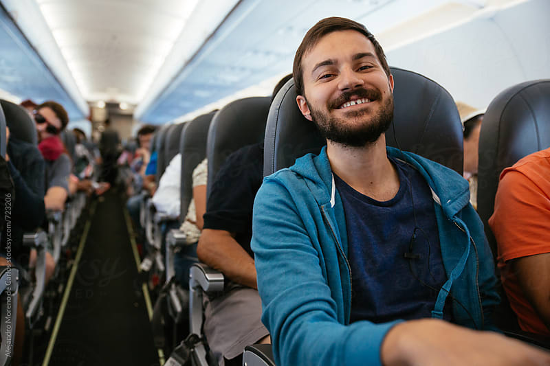 Young smiling man with headphones sitting on an airplane during a flight by Alejandro Moreno de Carlos for Stocksy United
