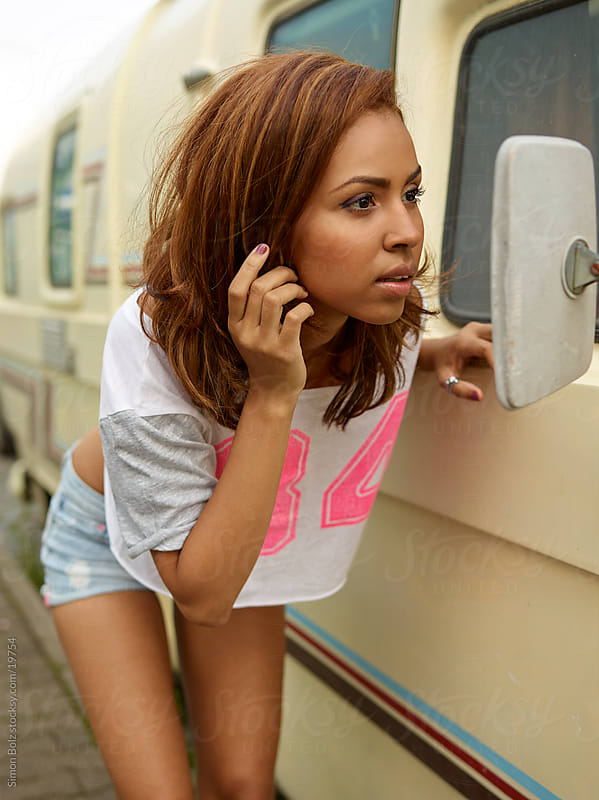 Brazilian girl looks in mirror of motorhome by Simon Bolz for Stocksy United