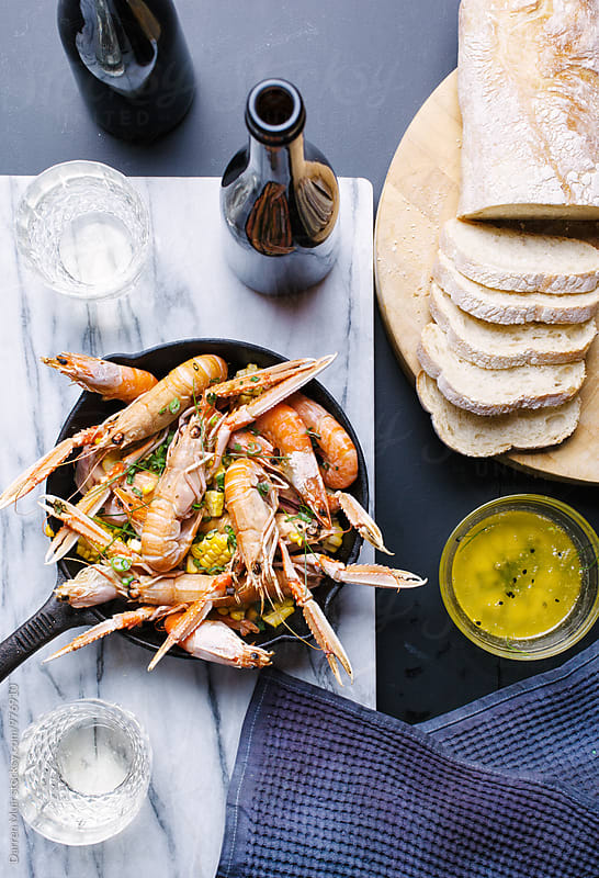 A seafood meal and drinks on a table,seen from above. by Darren Muir for Stocksy United