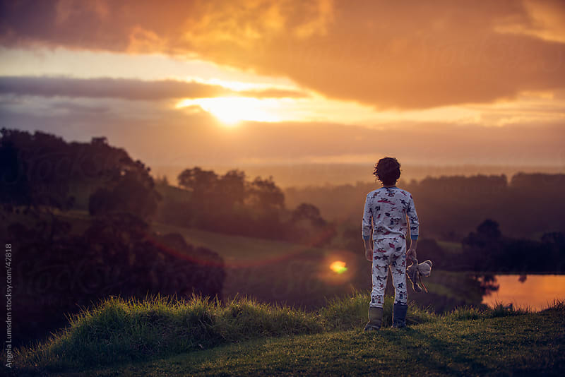 Young boy standing watching the sunset in the country by Angela Lumsden for Stocksy United