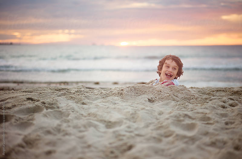 Young boy buried in sand at beach at sunset by Angela Lumsden for Stocksy United