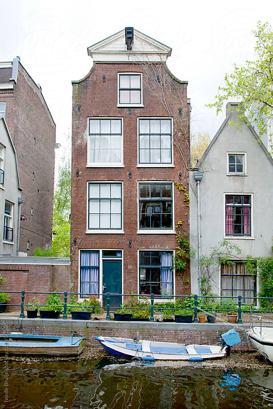 The facade of an old canal house in Amsterdam, surrounded by flowers and with a boat in front by Ivo de Bruijn for Stocksy United