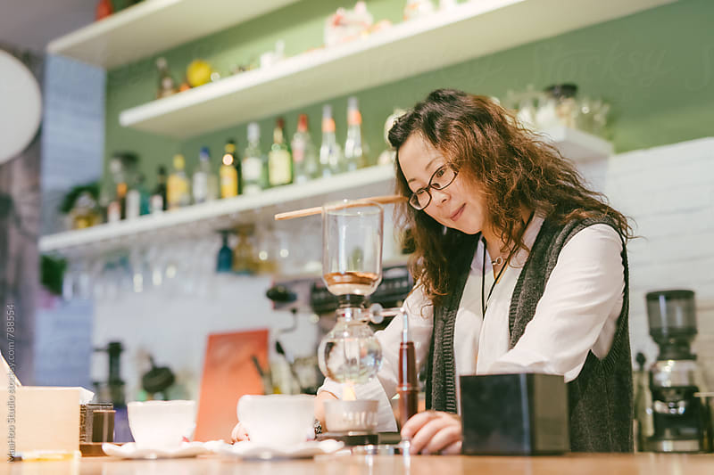 Female coffee shop owner preparing coffee at counter by Maa Hoo for Stocksy United