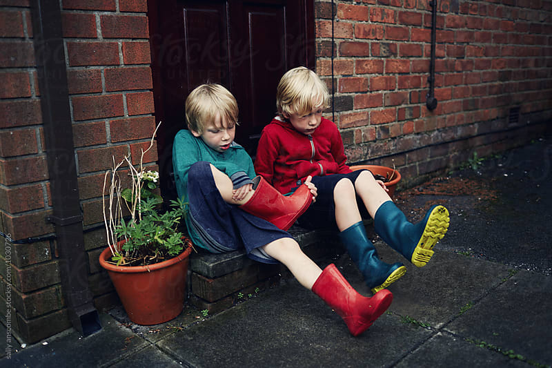 Children taking off their wellington boots by sally anscombe for Stocksy United