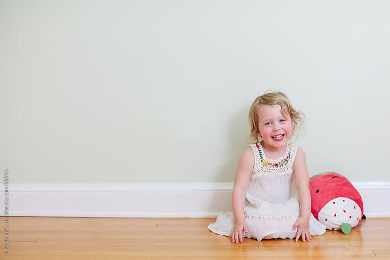 little girl with a smiling with her stuffed toy by Meaghan Curry for Stocksy United