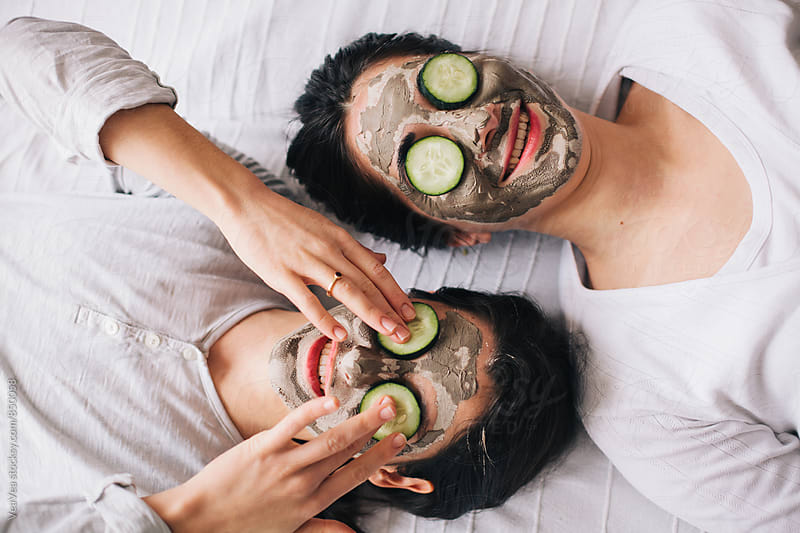 Two beautiful women with facial masks and cucumbers on their faces by VeaVea for Stocksy United