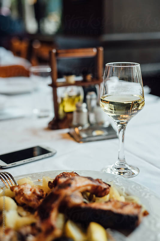Glass of wine and part of the meal by Boris Jovanovic for Stocksy United