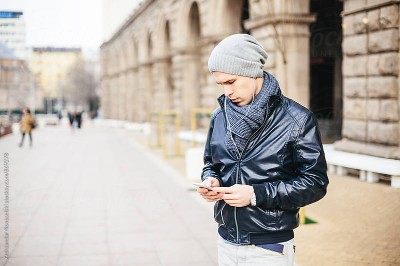 Young man texting on his phone on the street by Aleksandar Novoselski for Stocksy United