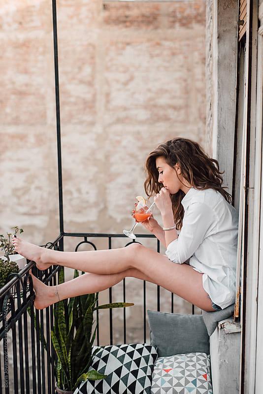 Beautiful woman drinking juice on the balkony by Boris Jovanovic for Stocksy United