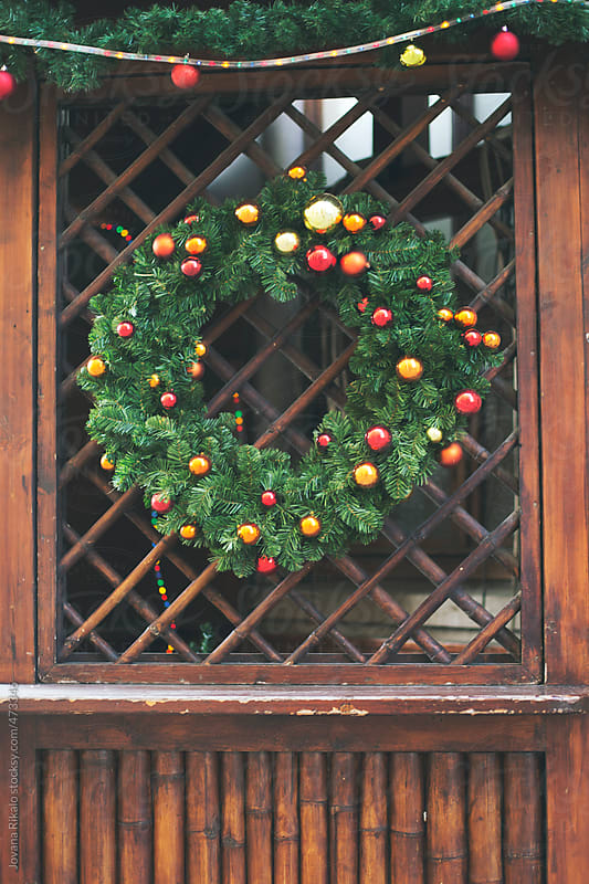 Christmas wreath hanging on a wooden door by Jovana Rikalo for Stocksy United