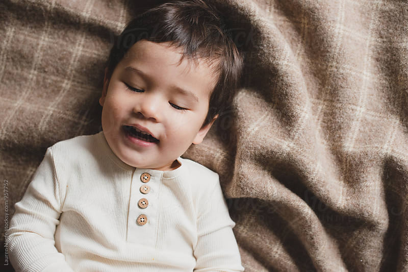 Portrait of little boy laughing by Lauren Naefe for Stocksy United