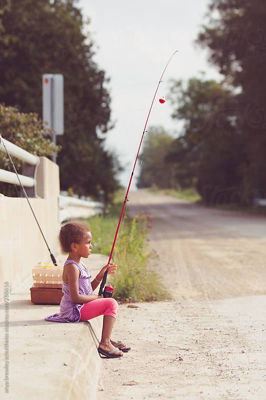 Portrait of a young girl sitting expectantly with a red fishing rod in her hand by anya brewley schultheiss for Stocksy United