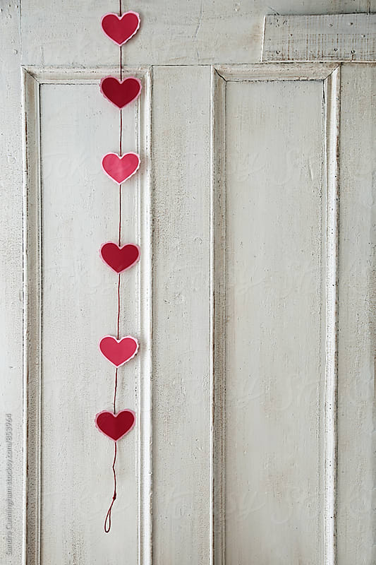 Paper heart garland on old white door by Sandra Cunningham for Stocksy United