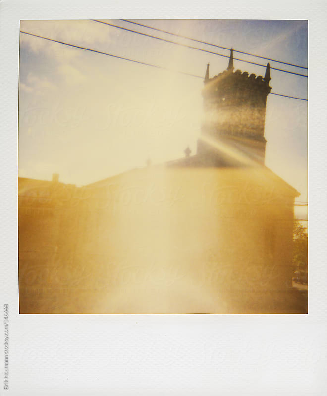 Polaroid of sun shining behind a church by Erik Naumann for Stocksy United