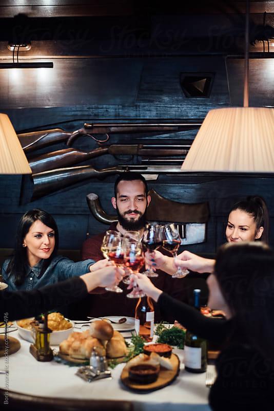 Friends having a toast in the restaurant by Boris Jovanovic for Stocksy United