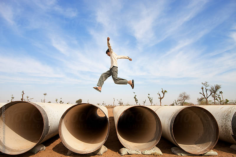 Boy jumping water pipes in the desert. India by Hugh Sitton for Stocksy United