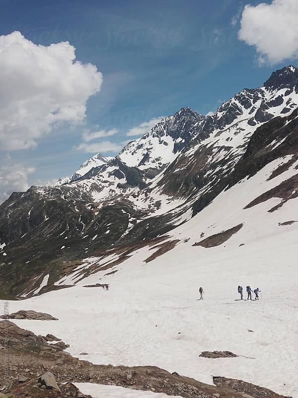 Trekkers Crossing Alpine Snow Field by Neil Warburton for Stocksy United