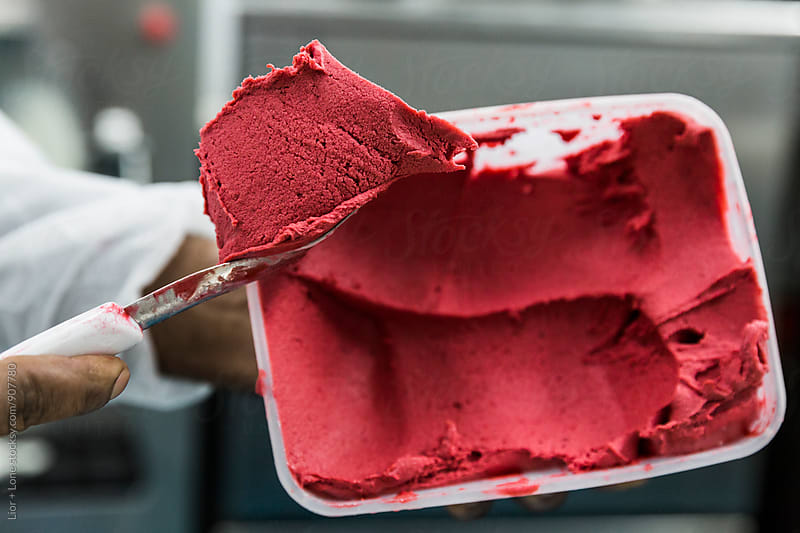 Closeup of hand scooping red strawberry ice cream from container by Lior + Lone for Stocksy United