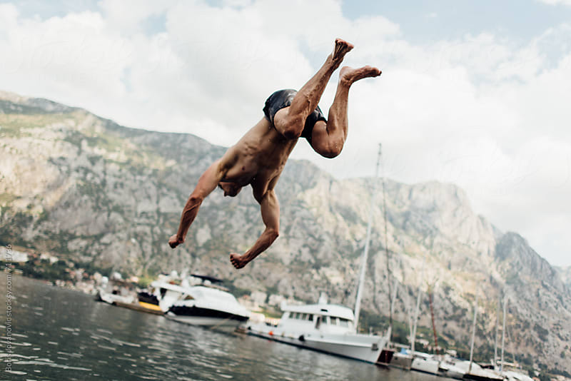Young man jumping in sea by Boris Jovanovic for Stocksy United