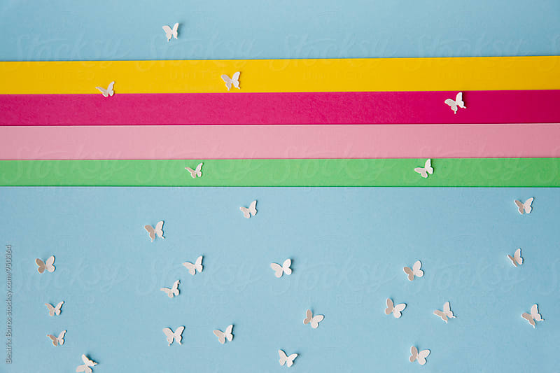 Paper butterflies flying on blue surface with stripes by Beatrix Boros for Stocksy United