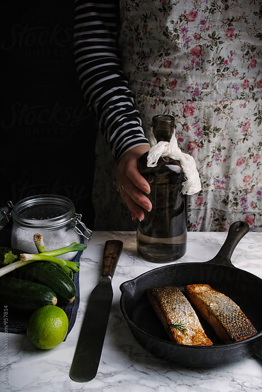 Woman preparing a salmon meal: by Darren Muir for Stocksy United
