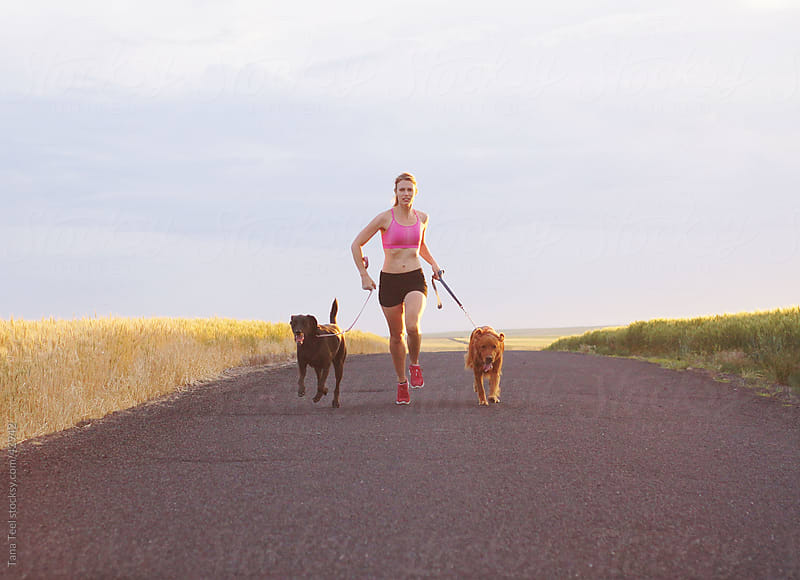 A woman running with her dogs by Tana Teel for Stocksy United