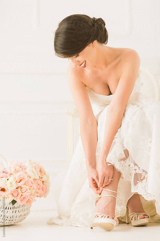 Smiling Bride Fastening Her Shoe by Lumina for Stocksy United