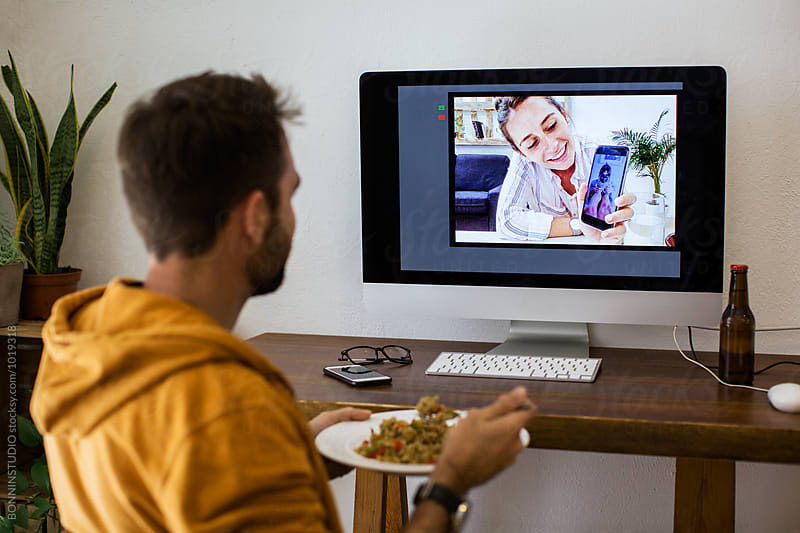 Young man making a video call with his girlfriend from home. by BONNINSTUDIO for Stocksy United
