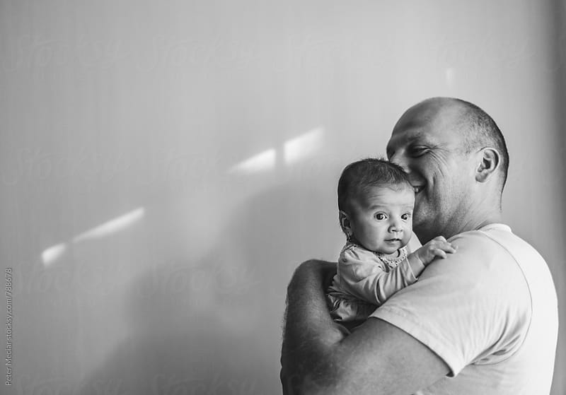 Father with little daughter on hands by Peter Meciar for Stocksy United