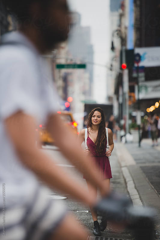 Young woman walking in busy city street by Lauren Naefe for Stocksy United