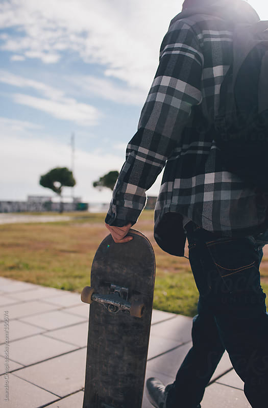Man with skate outdoors by Leandro Crespi for Stocksy United