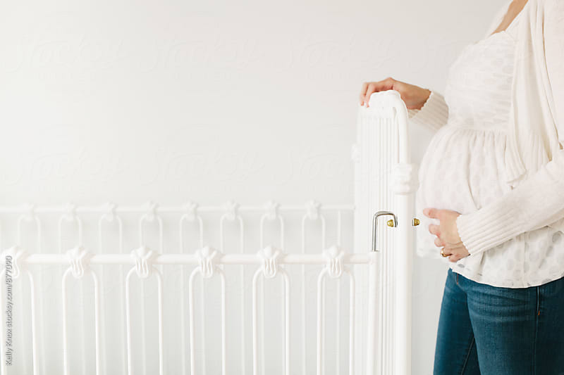 pregnant woman standing next to a crib in a nursery by Kelly Knox for Stocksy United