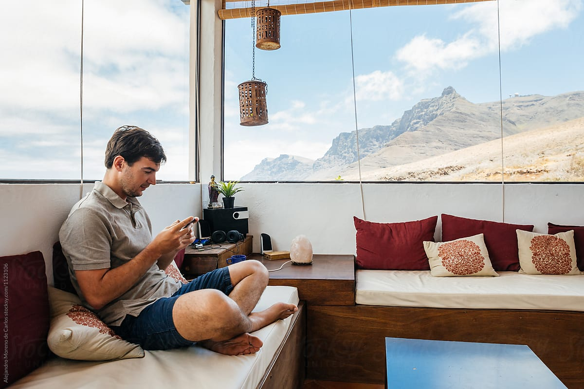 Amazing Man Using Smartphone On Luxury Home Sitting On A Sofa With Stunning  Mountain View Out Of
