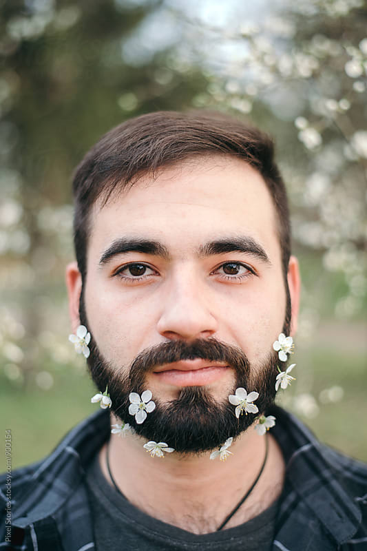Young man with Spring blossoms on beard by Pixel Stories for Stocksy United