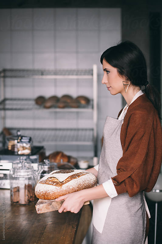 Saleswoman Offering Bread to Customers by Lumina for Stocksy United