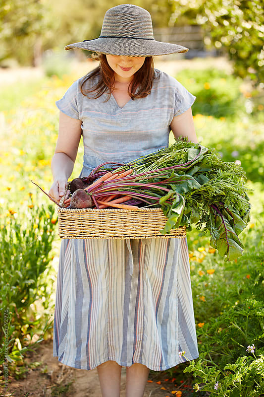 Woman farmer holding basket of organic veggies from farm by Trinette Reed for Stocksy United