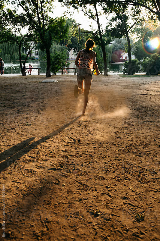 Teenager girl running away on a dusty field by Beatrix Boros for Stocksy United
