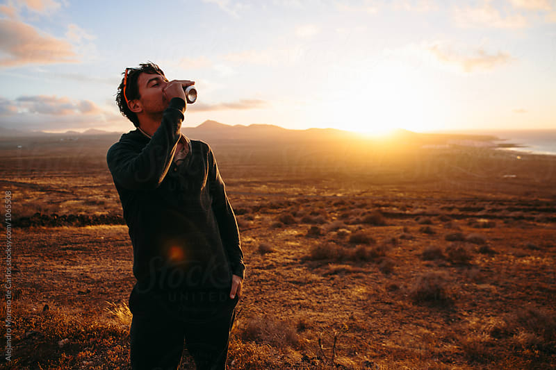 Adult man drinking from can against of sunset by Alejandro Moreno de Carlos for Stocksy United
