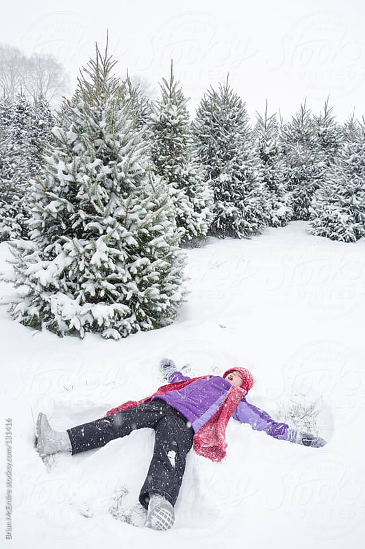 Little Girl Makes Snow Angel In Front of Many Christmas Trees Co by Brian McEntire for Stocksy United
