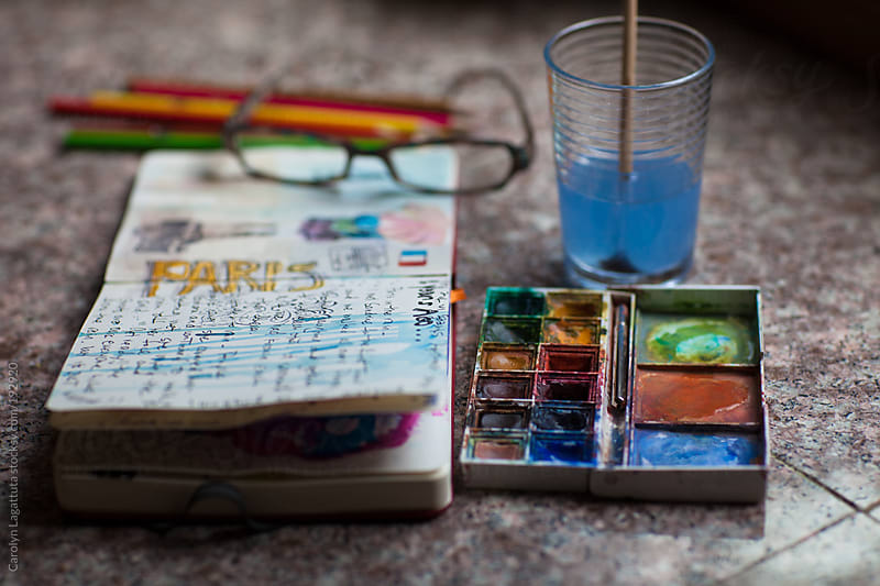 Journal open to a page about Paris with paint and pencils by Carolyn Lagattuta for Stocksy United