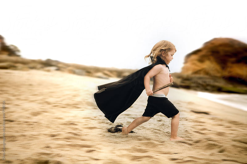 Boy Running Across Beach Wearing Black Cape by Dina Giangregorio for Stocksy United