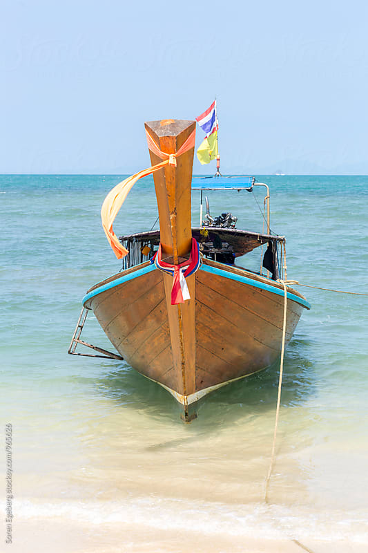 Longtail boat on a tropical beach  by Soren Egeberg for Stocksy United