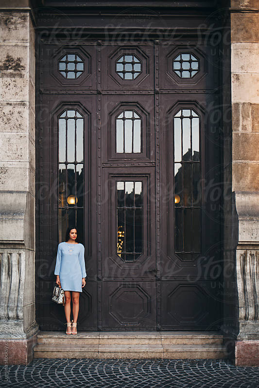 Elegant Woman Standing by a Large Metal Door by Lumina for Stocksy United