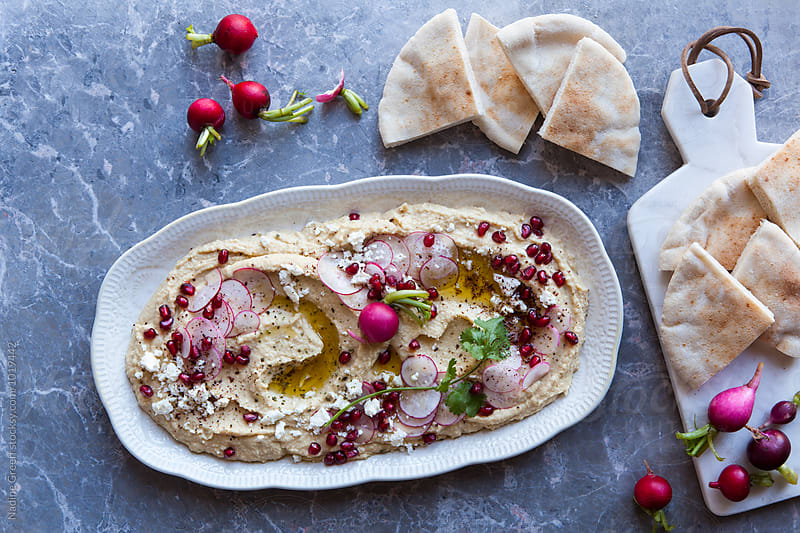 Pita bread with vegetable hummus dip by Nadine Greeff for Stocksy United
