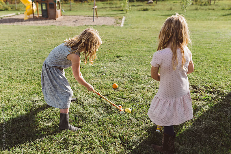 Sisters playing a game of croquet by Carey Shaw for Stocksy United